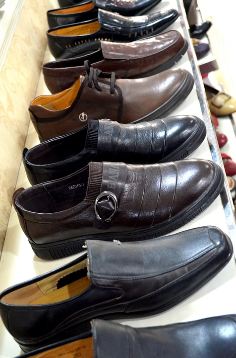 The picture portrays a row of men's shoes in a shoe store.